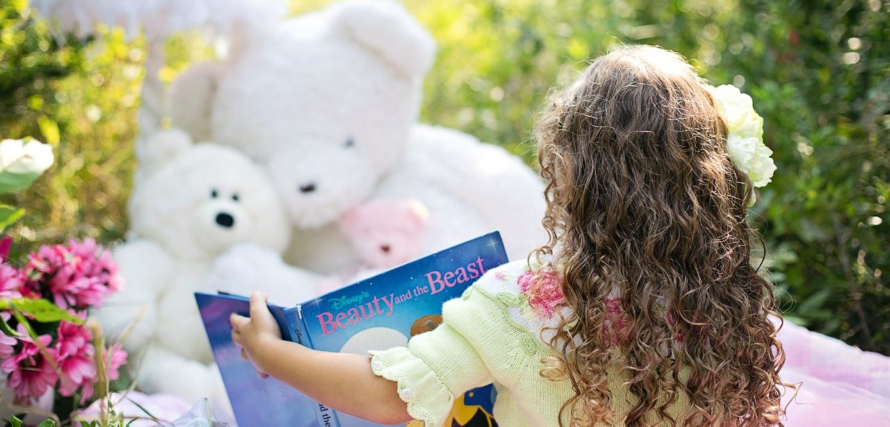 Little Girl Reading to Teddy Bears